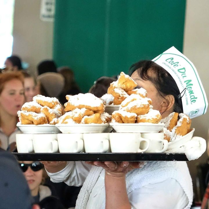 A server at New Orleans' legendary Cafe Du Monde carries a tray of coffee and fresh beignets.