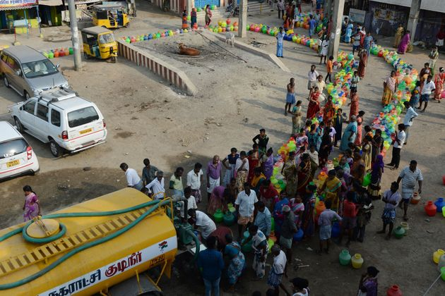 People queue to get drinking water from a tanker on the outskirts of