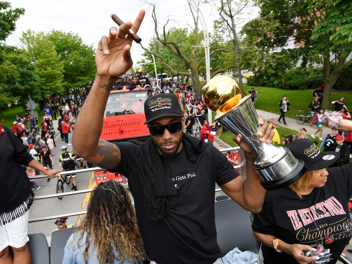Kawhi Leonard points to the sky with a cigar in one hand and his NBA Finals MVP trophy in the other during the Raptors victory parade in Toronto on June 17, 2019.