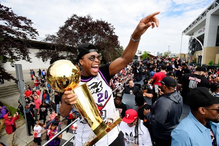 Kyle Lowry points to the crowd while smiling with the Larry O'Brien trophy in his hand during the Raptors parade in Toronto on June 17, 2019.