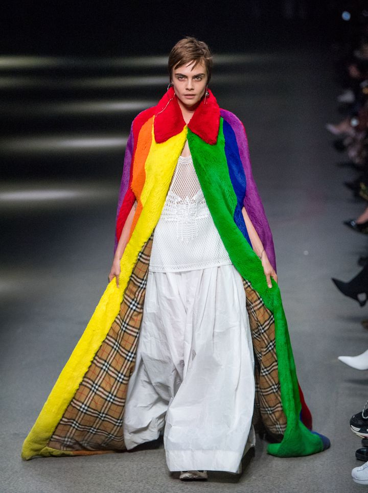 Cara Delevingne walks the runway at Burberry wearing a rainbow faux fur cape.