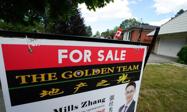 A for-sale sign in front of a house in Toronto, July 24,