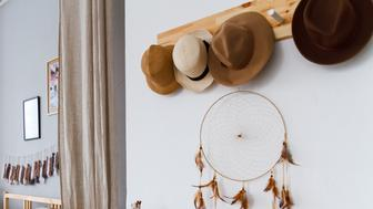 Hats and a dream catcher on the wall in a bright cozy bedroom
