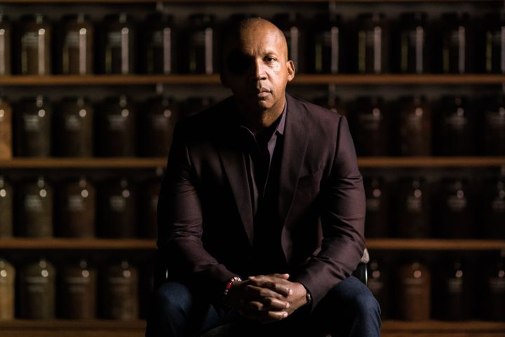 Bryan Stevenson sits in front of a wall of jars filled with soil collected from lynching sites across the country. The jars a