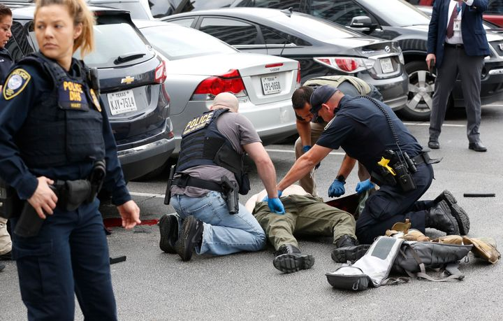 Law enforcement officers attend to an injured shooter in a parking lot after he fired shots at the Earle Cabell Federal Build