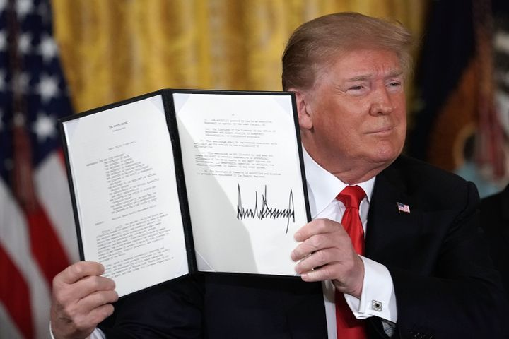 U.S. President Donald Trump holds up an executive order that he signed during a meeting of the National Space Council at the