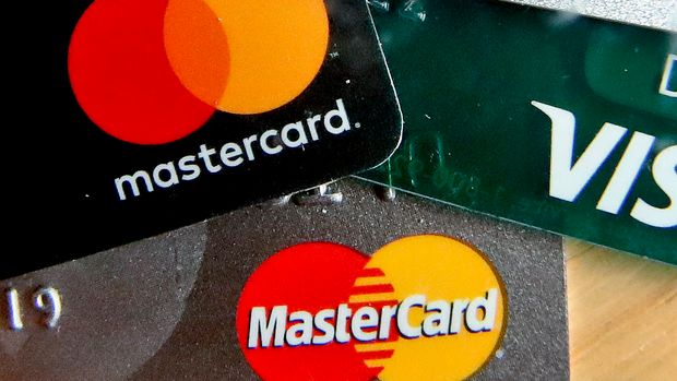 FILE - In this Feb. 20, 2019, file photo photo shows a logo for Mastercard on credit cards in Zelienople, Pa. Mastercard will allow transgender people to use their chosen names on credit cards in an effort to combat potential discrimination at the cash register. That means that the name on the credit card owned by a transgender person could be different than that found on their birth certificate or driver's license. (AP Photo/Keith Srakocic, File)