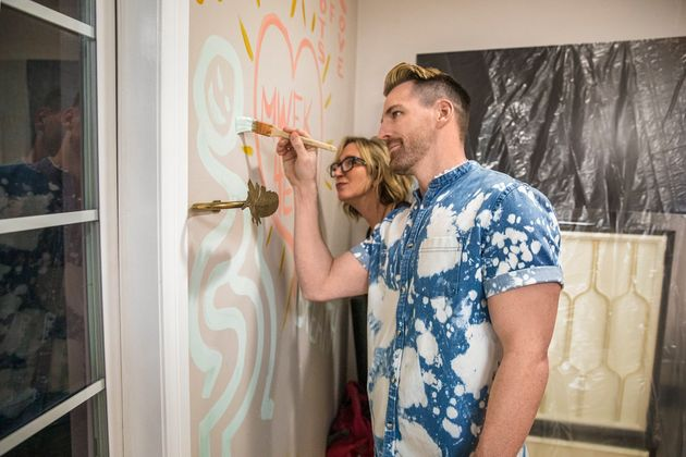 Orlando Soria and homeowner Kille burn sage in her bedroom while testing out new paint colors by painting...