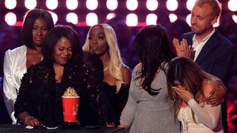 "Brie Miranda Bryant (2ndL) Senior VP, Unscripted Development and Programming at Lifetime, flanked by  Asante McGee (L), Lisa VanAllen (2ndR), Lizzette Martinez (R), and Faith Rodgers (3rdR), accepts the award for Best Documentary for ""Surviving R. Kelly"" onstage during the 2019 MTV Movie & TV Awards at the Barker Hangar in Santa Monica on June 15, 2019. - The 2019 MTV Movie & TV Awards were filmed on June 15 and air on June 17. (Photo by VALERIE MACON / AFP)        (Photo credit should read VALERIE MACON/AFP/Getty Images)"