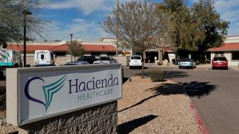 FILE - This Jan. 25, 2019, file photo, shows the Hacienda HealthCare facility in Phoenix. A legal claim against the state of Arizona by the parents of an incapacitated woman who was raped and later gave birth at Hacienda HealthCare alleges the facility and state broke promises to have only female caregivers tend to their daughter. The Arizona Health Care Cost Containment System declined to comment on the claim. (AP Photo/Matt York, File)