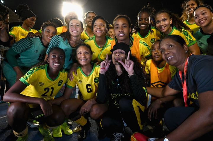 Cedella Marley (center) poses with members of the Jamaican women's national soccer team after a World Cup tune-up match