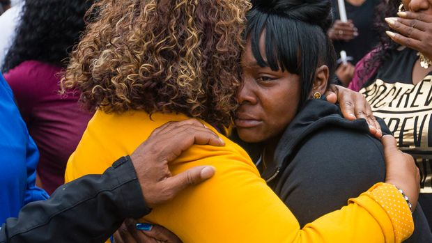 Family members embrace one another during a vigil for Eric Logan Monday, June 17, 2019 on Washington Street in South Bend, Ind.  Logan, 54, was killed in South Bend early Sunday after someone called police to report a suspicious person going through cars, according to the St. Joseph County prosecutor's office. (Michael Caterina/South Bend Tribune via AP)