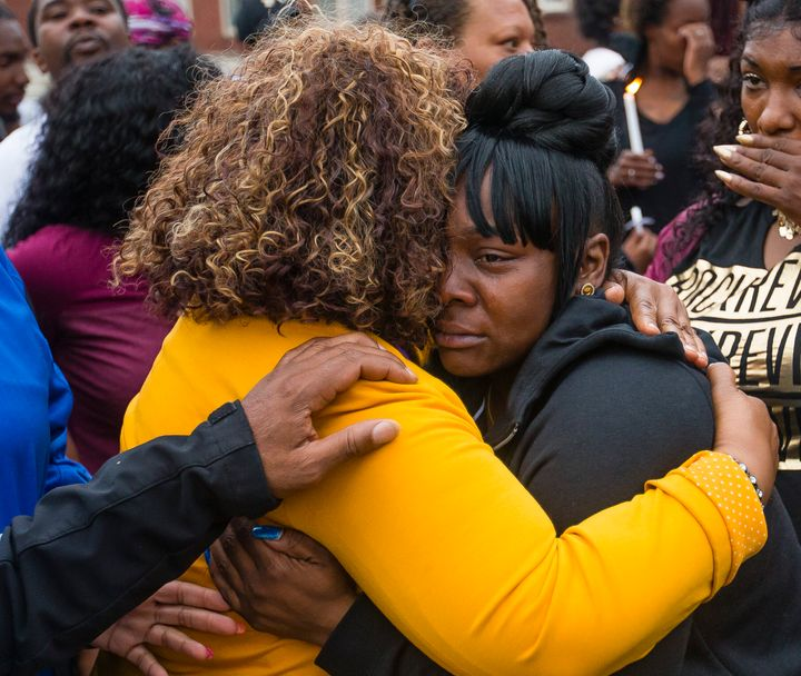 Family members embrace one another during a vigil for Eric Logan Monday, June 17, 2019, on Washington Street in South Bend, I