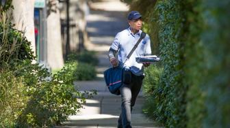 """A letter carrier with the U.S. Postal Service makes his rounds near the home of former president Barack Obama, Wednesday, Oct. 24, 2018, in Washington. The U.S. Secret Service says agents have intercepted packages containing """"possible explosive devices"""" addressed to Obama and Hillary Clinton. (AP Photo/Alex Brandon)"""