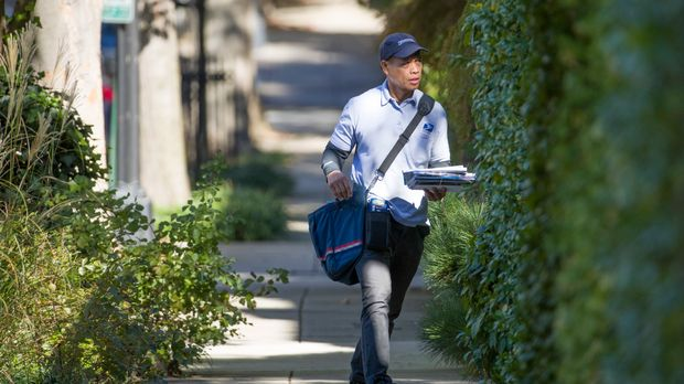 "A letter carrier with the U.S. Postal Service makes his rounds near the home of former president Barack Obama, Wednesday, Oct. 24, 2018, in Washington. The U.S. Secret Service says agents have intercepted packages containing ""possible explosive devices"" addressed to Obama and Hillary Clinton. (AP Photo/Alex Brandon)"