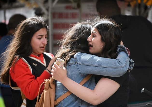 Friends embrace on the streets of Toronto after gunshots rang out during the Raptors victory parade on