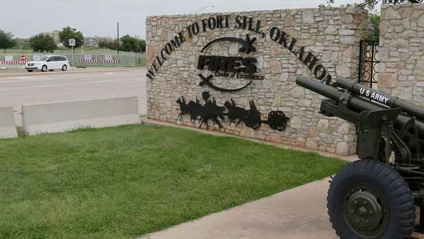 A vehicle drives by a sign at Scott Gate, one of the entrances to Fort Sill, in Fort Sill, Okla., Tuesday, June 17, 2014. The temporary housing of hundreds of immigrant children at Fort Sill and the influx of workers to take care of them could infuse millions of dollars into the local economy, city leaders said. (AP Photo/Sue Ogrocki)