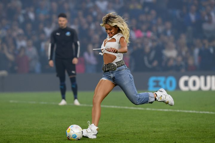 Ora kicking a ball on the field.