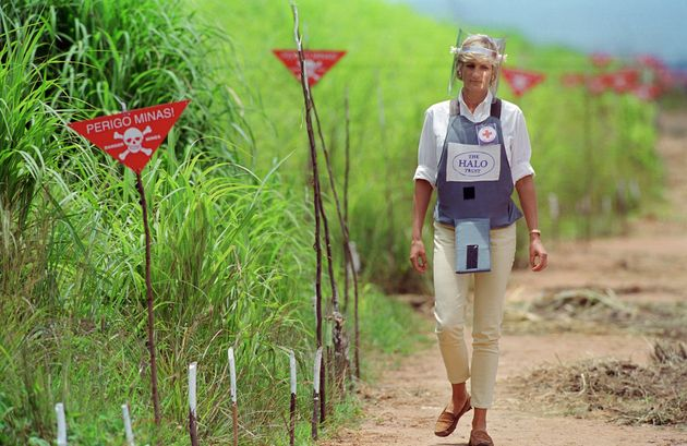Princess Diana, wearing protective body armour and a visor, visits a landmine minefield being cleared...
