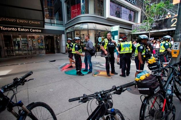 Police help disperse crowds near Eaton Centre after a shooting disrupted at the Toronto Raptors celebration...