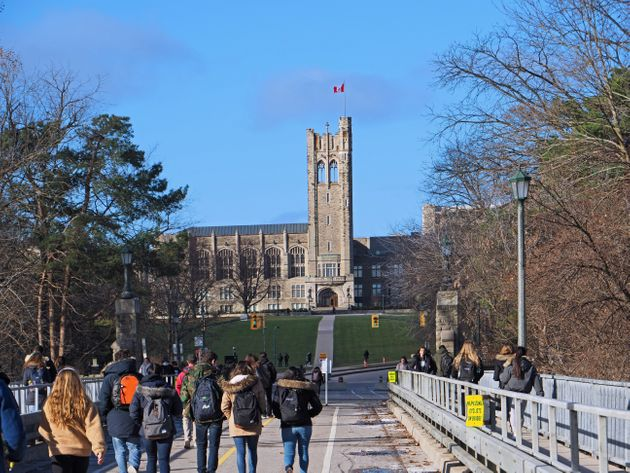 Students walking toward the gothic tower of University College at Ontario's Western University on Dec....