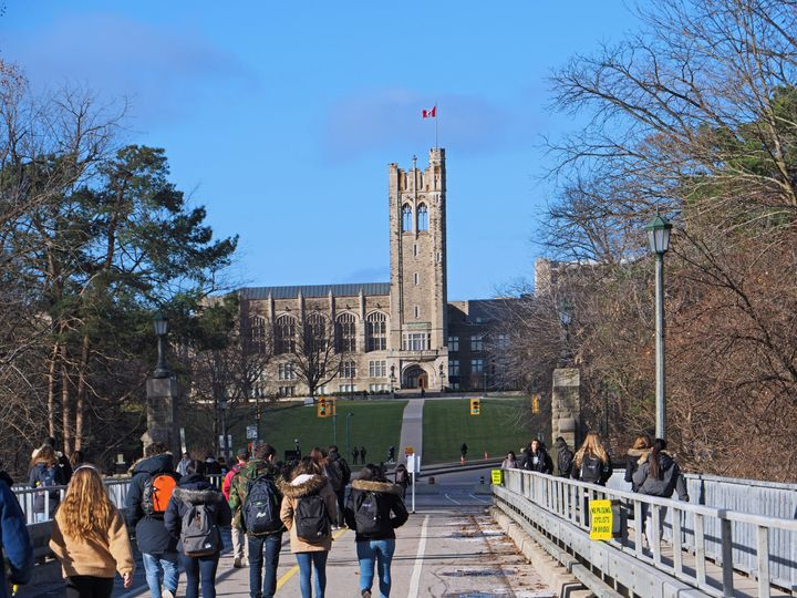 Students walking toward the gothic tower of University College at Ontario's Western University on Dec. 4, 2018.