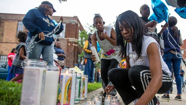 Sherika Logan lights candles for her uncle during a vigil for Eric Logan Monday, June 17, 2019 on Washington Street in South Bend, Ind.  Logan, 54, was killed in South Bend early Sunday after someone called police to report a suspicious person going through cars, according to the St. Joseph County prosecutor's office. (Michael Caterina/South Bend Tribune via AP)