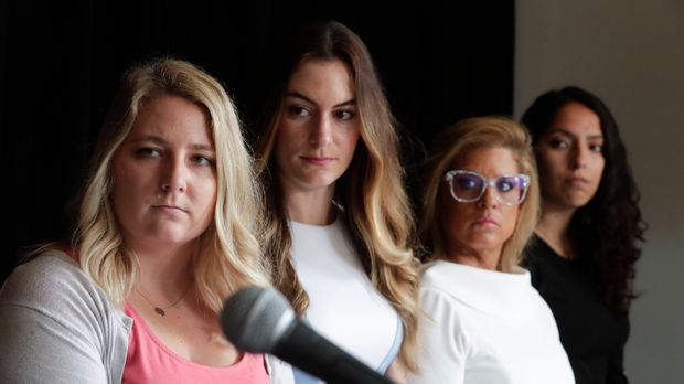 Gabrielle McLemore, left, Niki DaSilva left center, Rep. Mara Candelaria Reardon, right center, and Samantha Lozano listen as their attorney announces during a press conference in Indianapolis Tuesday, June 18, 2019, a lawsuit against Indiana Attorney General Curtis Hill and the State of Indiana on behalf of four women who accused the attorney general of drunkenly groping them at a party. (AP Photo/Michael Conroy)