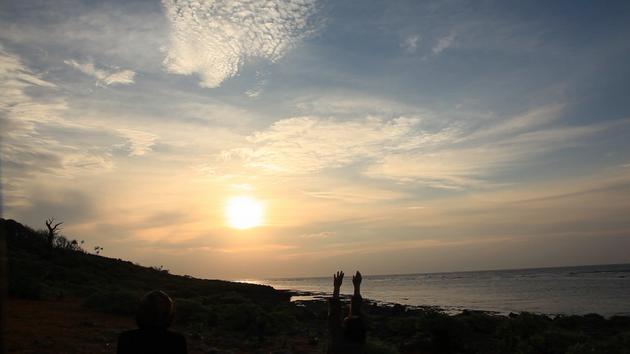 沖縄・久高島で海辺の朝日に向かう田中さん