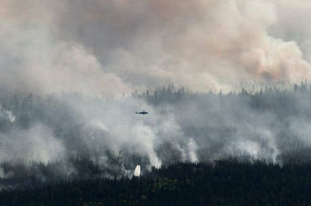 A helicopter is seen dropping water on the Chuckegg Creek wildfire west of High Level, Alta., on May...