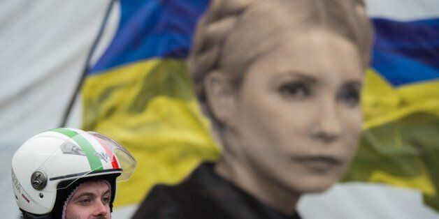 An anti-government protester stands in front of a portrait of jailed former Ukrainian Prime minister...