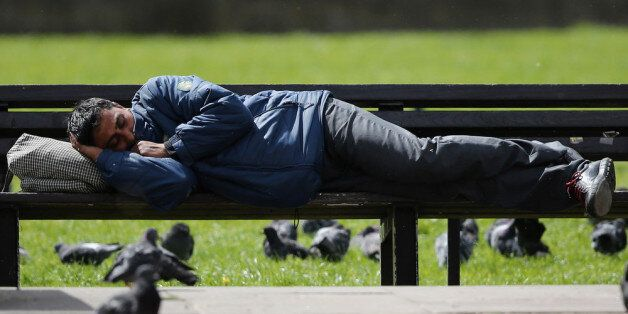 LONDON, ENGLAND - MAY 09: A man sleeps on a bench as groups of Eastern Europeans gather in Marble Arch...