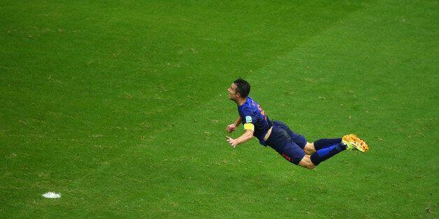 Netherlands' forward Arjen Robben (R) celebrates after scoring agaisnt Spain's goalkeeper Iker Casillas...