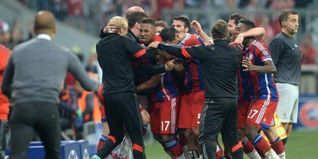 Bayern Munich's team members celebrate after Jerome Boateng (C) scored during the first leg UEFA Champions...