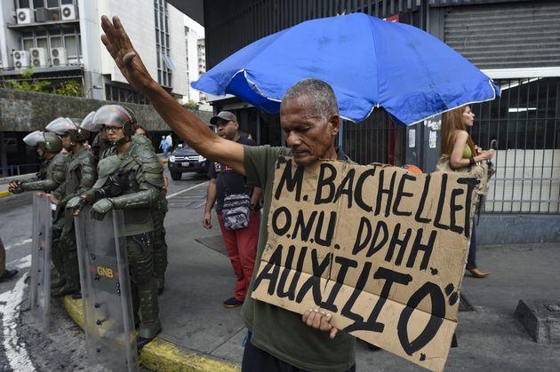 Un trabajador del sector del petróleo se manifiesta pidiendo ayuda a Michelle Bachelet, en