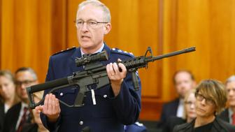FILE - In this April 2, 2019, file photo, Police acting superintendent Mike McIlraith shows New Zealand lawmakers in Wellington, New Zealand, an AR-15 style rifle similar to one of the weapons a gunman used to slaughter 50 people at two mosques. New Zealand's new gun laws have been signed into law and now ban military-style weapons, just one day after the nation's parliament overwhelmingly approved legislation to outlaw them less than a month after a man used such guns to kill 50 worshippers at two mosques. (AP Photo/Nick Perry, File)