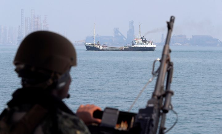 A U.S. Navy soldier onboard a patrol boat stands guard as an oil tanker makes its way towards Bahrain's port, Bahrain, Sept. 11, 2018.