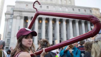 Chaney Trotter carries a giant a coat hanger during a protest against abortion bans, Tuesday, May 21, 2019, in New York. Abortion rights supporters held rallies across the country Tuesday in opposition to the wave of sweeping abortion bans being enacted this year in Midwestern and Southern states. (AP Photo/Mary Altaffer)