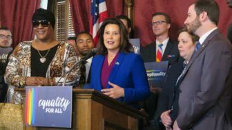 "Michigan Gov. Gretchen Whitmer, center, joins with lawmakers and others calling for expanding the state's civil rights law to prohibit discrimination against LGBT people on Tuesday, June 4, 2019, in the Capitol building in Lansing, Mich. The Democratic governor says nobody should be fired from a job or be evicted ""based on who they love or how they identify."" (AP Photo/David Eggert)"