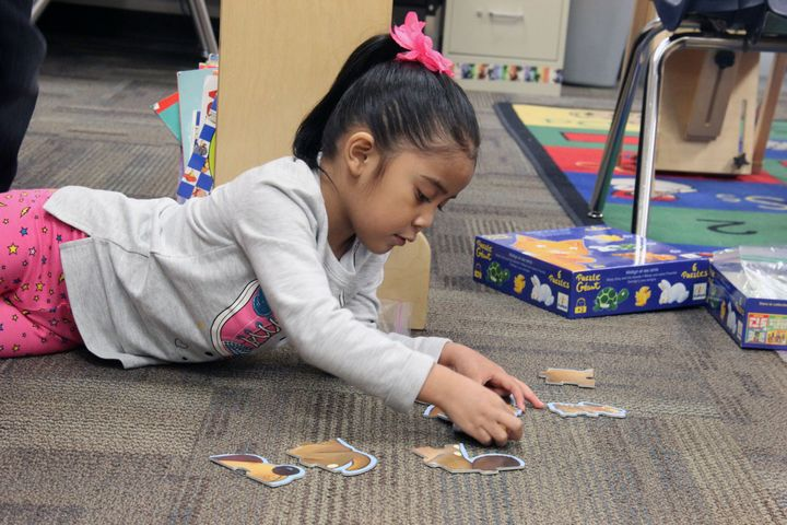 A student in Ashley Navarette's preschool class plays with a puzzle after eating breakfast.