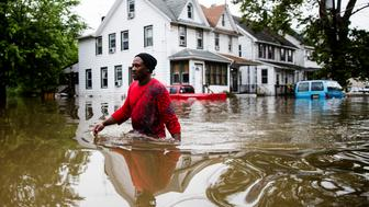 Chris Smith makes his way through floodwaters to the Macedonia Baptist Church in Westville, N.J., Thursday, June 20, 2019. Severe storms containing heavy rains and strong winds spurred flooding across southern New Jersey, disrupting travel and damaging some property. (AP Photo/Matt Rourke)