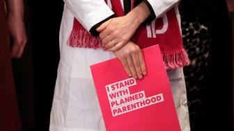 "FILE - In this, Feb. 25, 2019, file photo, Dr. Erin Berry, Washington State Medical Director for Planned Parenthood of the Great Northwest and the Hawaiian Islands, holds a folder as she listens at a news conference announcing a lawsuit challenging the Trump administration's Title X ""gag rule"" in Seattle. A U.S. appeals court says new Trump administration rules imposing additional hurdles for women seeking abortions can take effect. Courts in Washington, Oregon and California had blocked the rules from taking effect. The rules ban taxpayer-funded clinics from making abortion referrals and prohibit clinics that receive federal money from sharing office space with abortion providers. The 9th U.S. Circuit Court of Appeals on Thursday said the lower courts appeared to have gotten the rulings wrong. (AP Photo/Elaine Thompson, File)"
