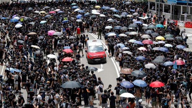 A taxi makes its way through a crowd of protesters gathered on a street near government offices in Hong Kong  Friday, June 21, 2019. Several hundred mainly student protesters gathered outside Hong Kong government offices Friday morning, with some blocking traffic on a major thoroughfare, after a deadline passed for meeting their demands related to controversial extradition legislation that many see as eroding the territory's judicial independence. (AP Photo/Kin Cheung)