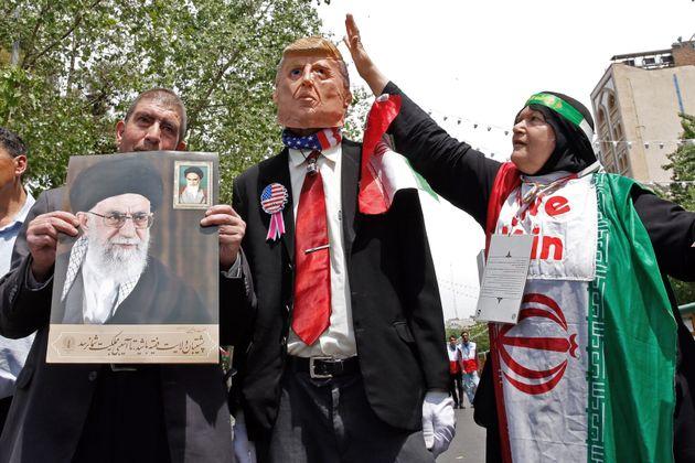 Manifestantes iraníes contra las sanciones de EEUU, portando retratos del ayatolá Ali Khamenei...