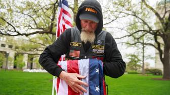 INDIANAPOLIS, INDIANA, UNITED STATES - 2019/04/27: A member of the AAF III% militia folds the American flag, which was soaked by rain, after the Pro-Freedom rally at the Indiana Statehouse during the during the third day of the National Rifle Association convention being held nearby. (Photo by Jeremy Hogan/SOPA Images/LightRocket via Getty Images)