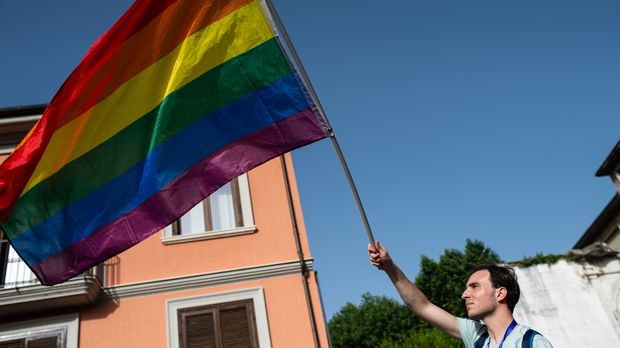 "AVELLINO, ITALY - JUNE 15: An LGBT activist waves the flag with the colors of the rainbow during the Avellino Pride 2019 on June 15, 2019 in Atripalda, Italy. ""Abellinum Pride 2019 - People Have The Power"" is the march in favor of LGBT rights organized by the Avellino movements in memory of the Stonewall riots of 1969, with godmothers of the event Eva Grimaldi and his wife Imma Battaglia. (Photo by Ivan Romano/Getty Images)"