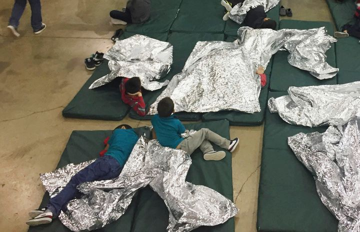 A June 17, 2018, file photo from U.S. Customs and Border Protection shows migrants being kept in a cage at a facility in McAllen, Texas. A year later, migrants still describe sleeping on floors under bright lights that shine 24/7, with nothing but Mylar blankets to keep warm.