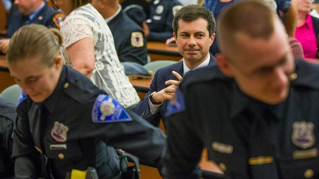 Democratic Presidential candidate and South Bend, Indiana Mayor Pete Buttigieg sits behind officers following a swearing-in ceremony on Wednesday, June 19, 2019, during a Board of Public Safety meeting inside the South Bend Police Department in South Bend, Ind. (Robert Franklin/South Bend Tribune via AP)
