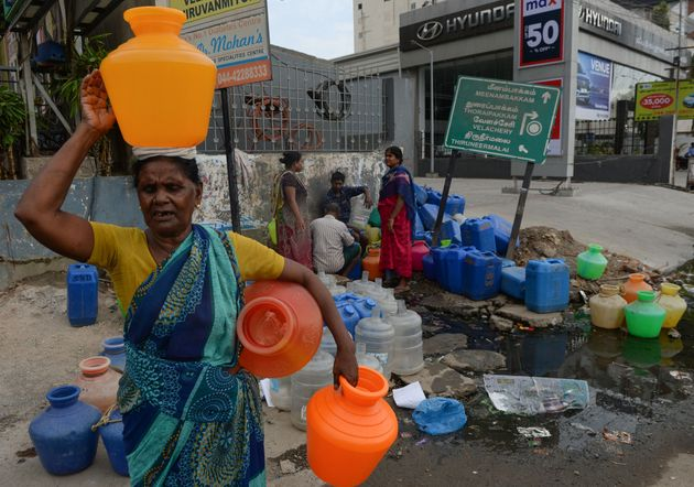People wait to get water at a distribution point in