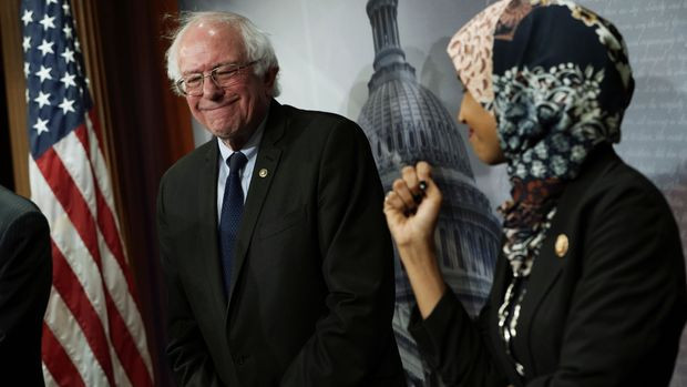 "WASHINGTON, DC - JANUARY 10:   U.S. Rep. Ilhan Omar (D-MN)  (R) and Sen. Bernie Sanders (I-VT) (L) share a moment during a news conference on prescription drugs January 10, 2019 at the Capitol in Washington, DC. Congressional Democrats held a news conference to introduce a legislative package ""that would drastically reduce prescription drug prices in the United States."" (Photo by Alex Wong/Getty Images)"